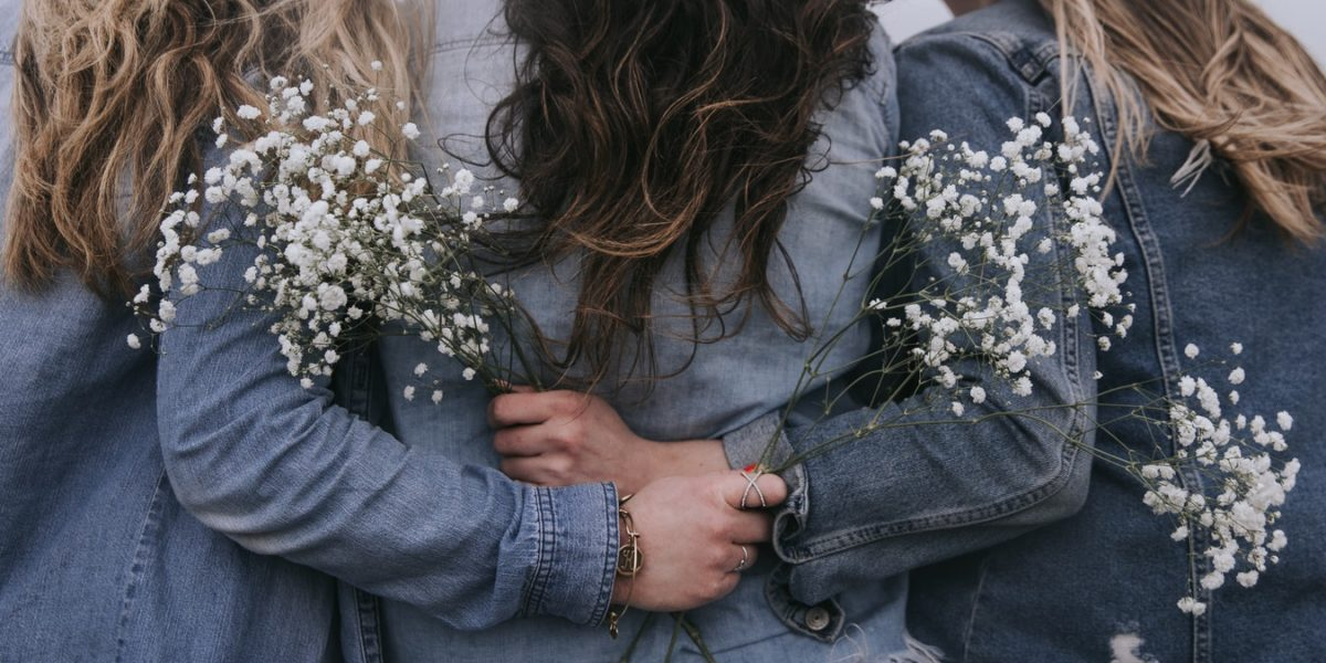 Tre donne di spalle si stringono in un abbraccio.