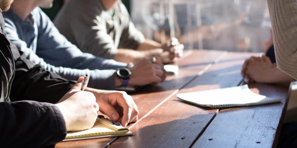 Tre uomini e una donna seduti intorno ad un tavolo.