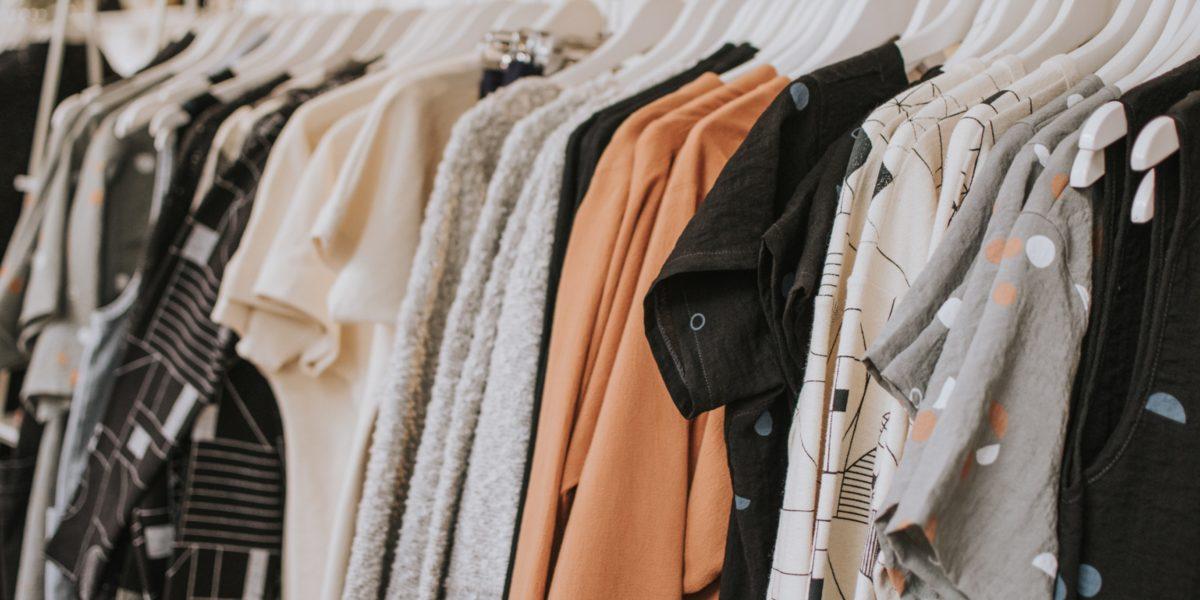 L'industria della moda inquina e compriamo troppi capi di abbigliamento. Appendiabiti con magliette colorate.