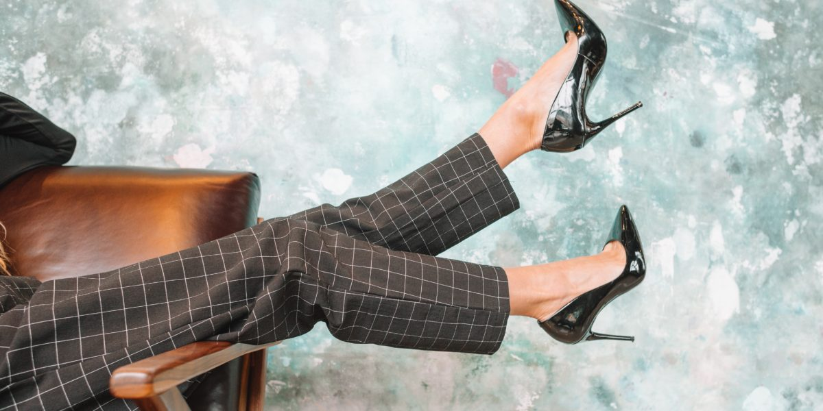 Una donna seduta su una poltrona indossa delle scarpe con tacchi alti.