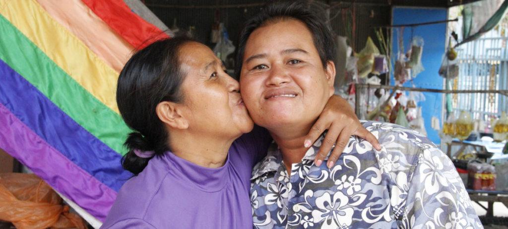 """L'ONU presenta il rapporto """"Families in a changing world"""". Due done si baciano davanti ad una bandiera arcobaleno."""