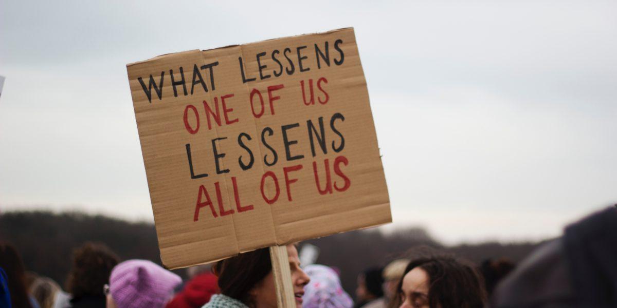 """Una donna durante una manifestazione regge un cartello con la scritta """"What lessens one of us lessens all of us""""."""