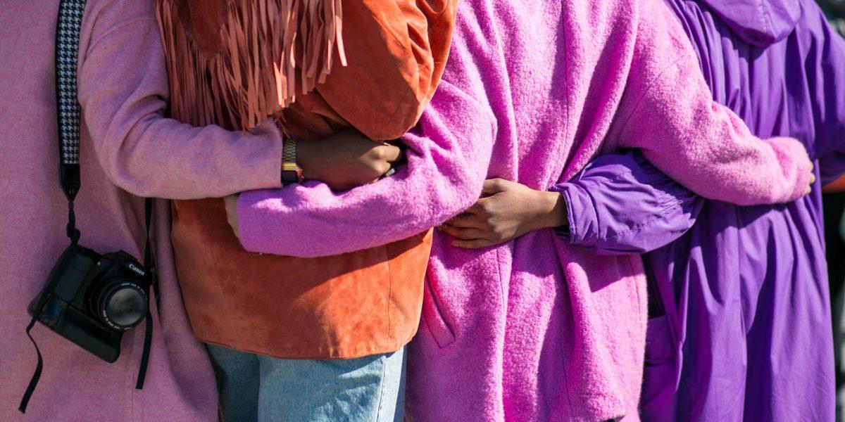 Donne abbracciate riprese di schiena.