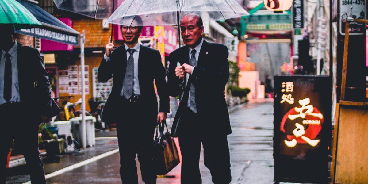 Uomini giapponesi camminano per strada.