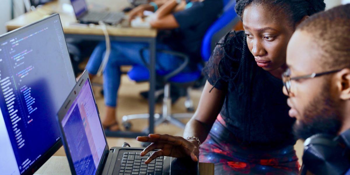 Un uomo e donna di colore lavorano a un computer.