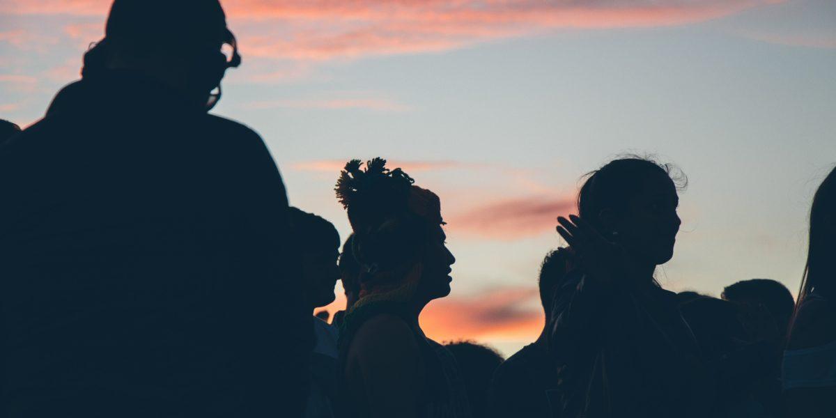 Gruppo di persone riprese al tramonto.