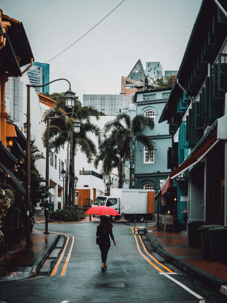 una donna cammina per la strada con un ombrello rosso.