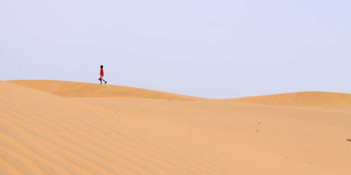 persona che cammina nel deserto.
