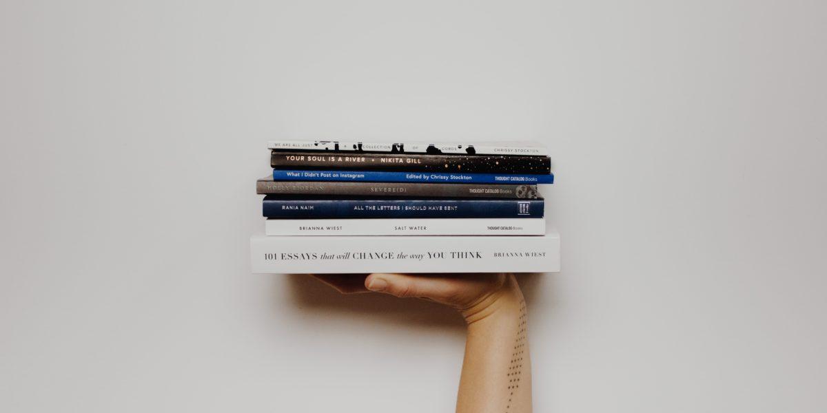 Pila di libri sostenuta da una mano