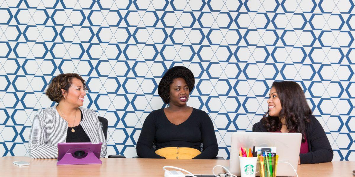 Donne sedute ad un tavolo davanti a dei laptop. La  parità nei consigli di amministrazione si fa attendere.