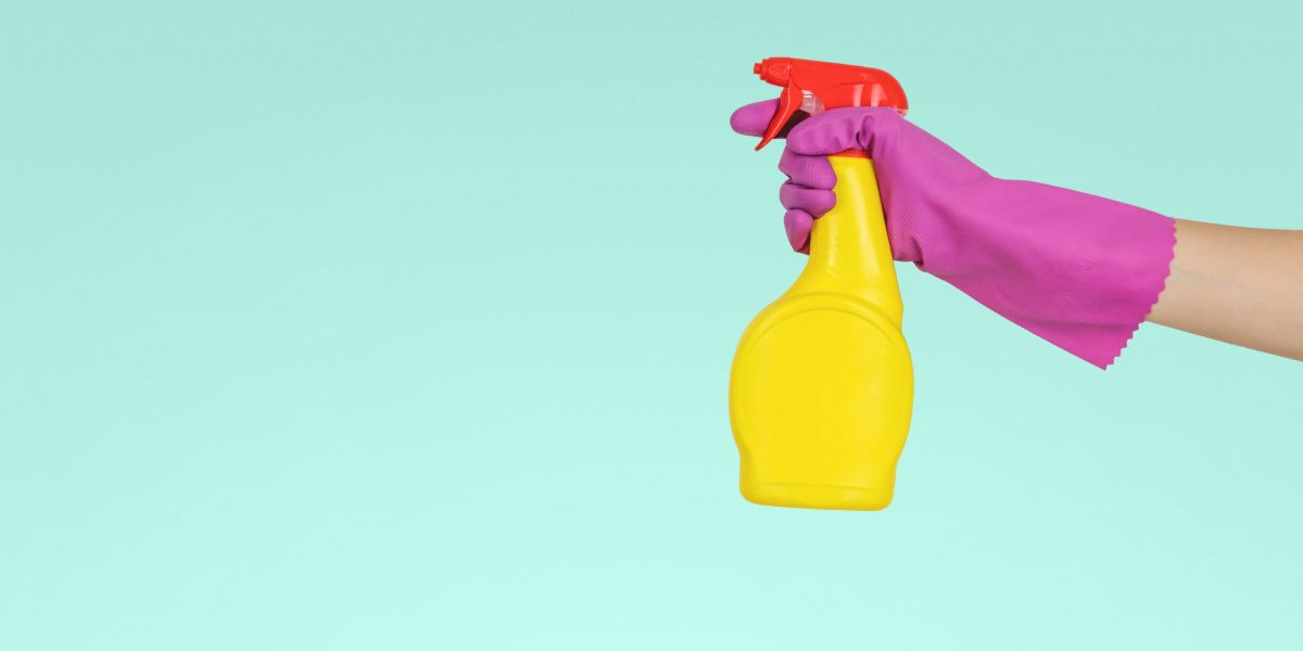 Una mano femminile impugna uno spruzzino. Le donne svolgono gran parte del lavoro domestico e di cura.