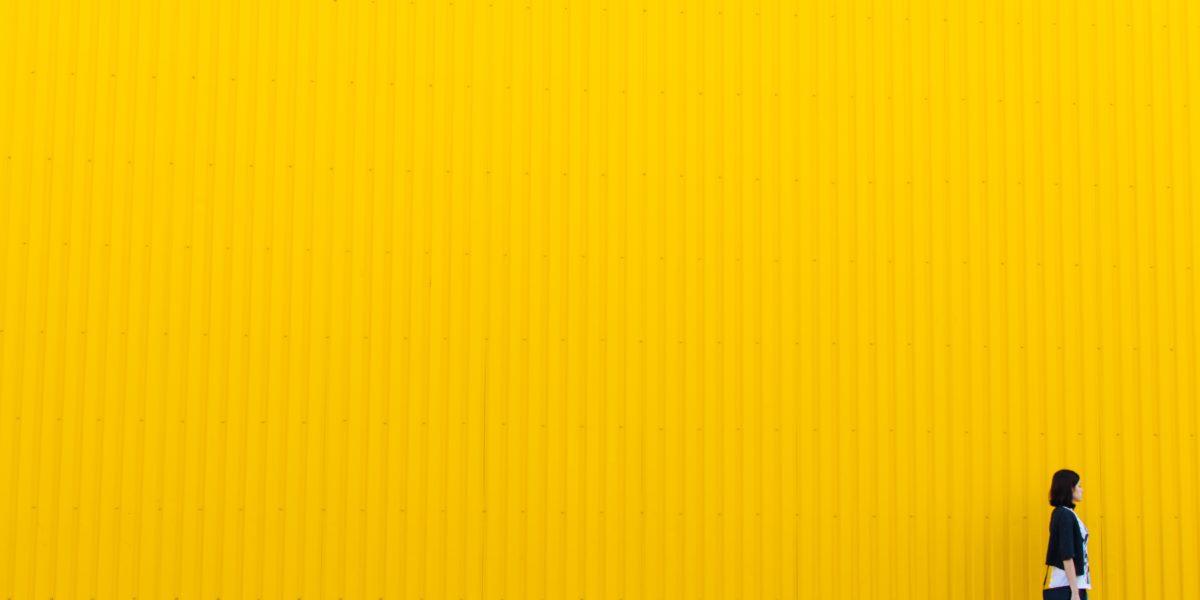 Donne che cammina lungo un muro giallo.