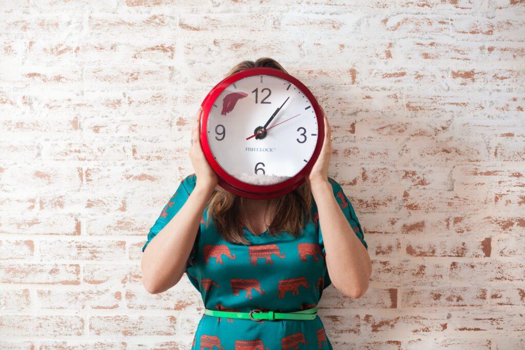 Una donna sorregge un orologio.